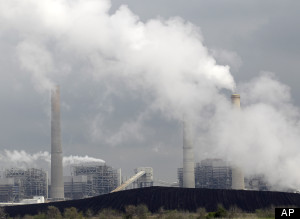 In this March 16, 2011  photo, exhaust rises from smokestacks in front of piles of coal at NRG Energy's W.A. Parish Electric Generating Station in Thompsons, Texas.  (AP Photo/David J. Phillip, originally viewed at www.onepennysheet.com)